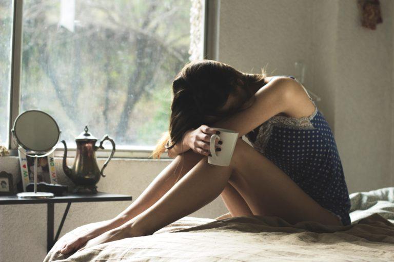 ベッドの上で屈み込む女性