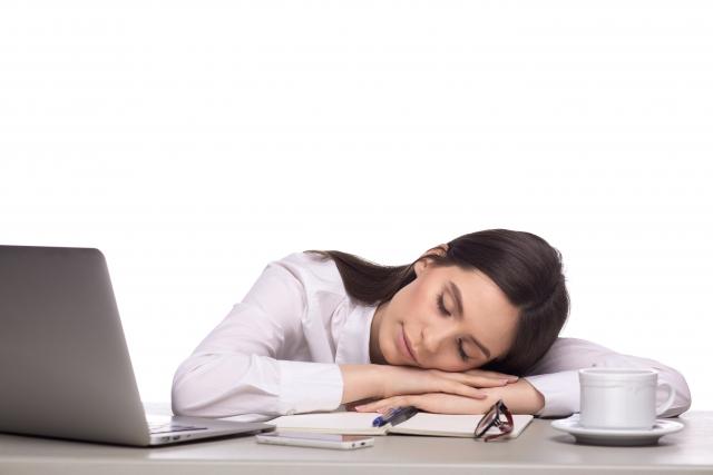 机のうつ伏せで寝る女性
